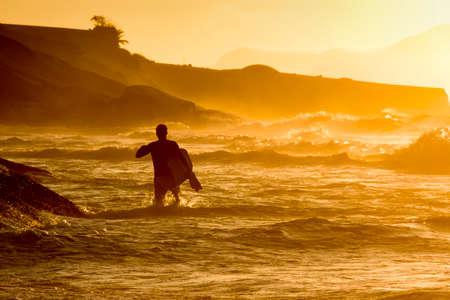 bodyboarder: Bodyboarder walkimg in the water at Ipanema tropical sunrise in Rio de Janeiro