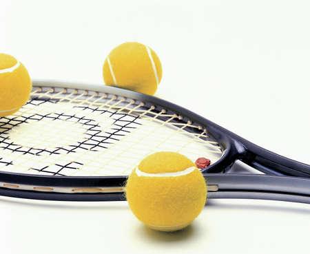 Tenis racquet and yellow tennis balls