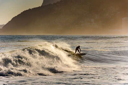 Surfer alone on the beach of Ipanema in Rio de Janeiro during the late afternoon
