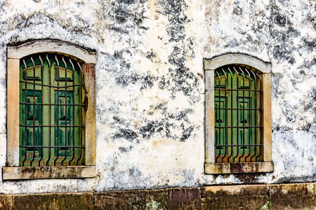 Old and aged historic wooden church windows with stone frame and grids in the city of Ouro Preto, Minas Gerais with a stone frame Stok Fotoğraf