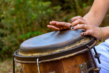 Woman percussionist playing a drum called atabaque during brazilian folk music performance