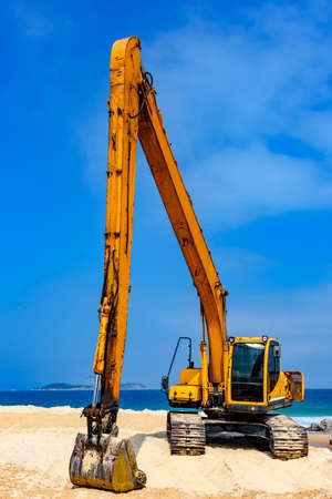 Yellow excavator cabin and arm over sand at beach in a sunny day