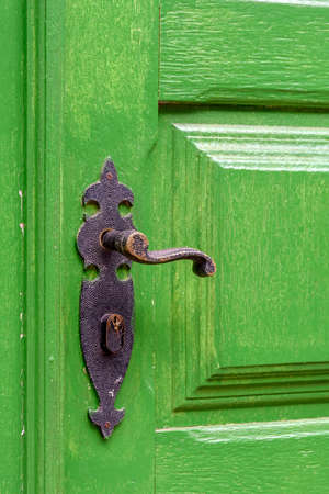 Old and aged green wooden door and door handle in the city of Ouro Preto, Minas Gerais with its rusty metal part.