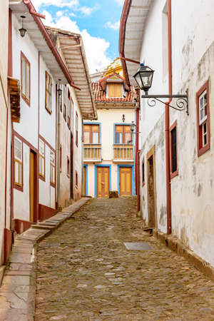 Facade of old houses built in colonial architecture with their balconies, roofs, colorful details and cobblestone street in the historical city of Ouro Preto in Minas Gerais.