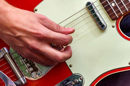 Hands and fingers playing eletric guitar during a bands performance at a rock concert