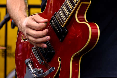Hands playing eletric guitar during a bands performance at a rock concert
