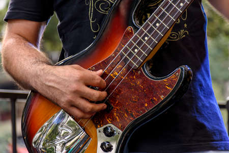 Hands playing eletric bass during a bands performance at a rock concert Stock Photo