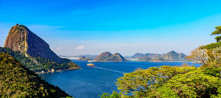 Cargo ship arriving at the entrance of the Guanabara Bay in Rio de Janeiro with forest, Sugar Loaf mountain and Niteroi city in background 写真素材