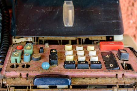 Old, rusty and damaged mechanical calculating machine left in the garbage dump