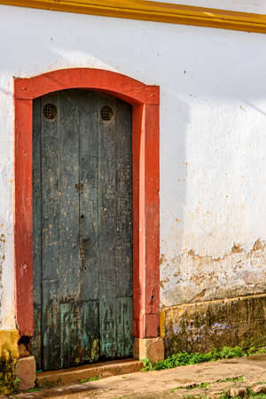 Old wooden door in a house with colonial architecture worn by time in the city of Tiradentes, state of Minas Gerais