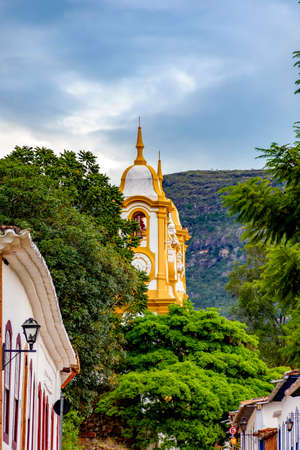 Historic 18th century church tower seen through trees and houses in the old city of Tiradentes in Minas Gerais, Brazil