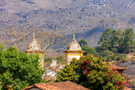 One church tower of the many historic churches in baroque and colonial style from the 18th century amid the hills and vegetation of the city Ouro Preto in Minas Gerais, Brazil
