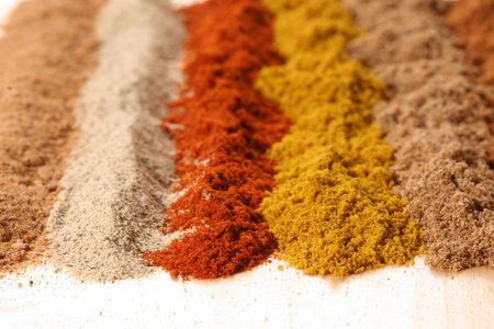 flavouring: right to left: cinnamon, coriander, curry, paprika, white pepper, nutmeg Stock Photo