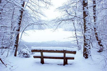 aloneness: Park bench in the snow with a pool in the background Stock Photo
