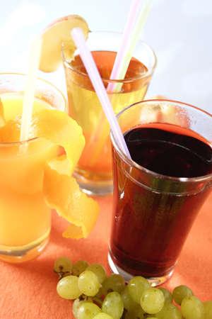 quencher: Glass of apple juice, orange juice and grape juice