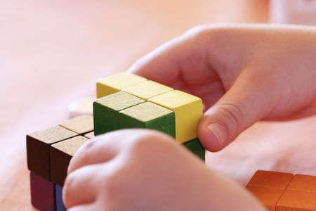 lacquered: childs hands buliding a cube with gaming pieces