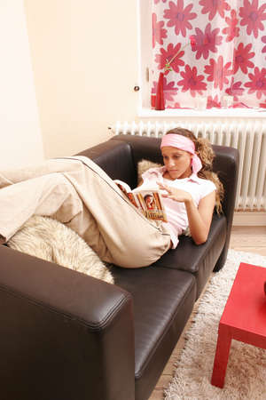 fifteen year old: Fifteen year old girl reading on the sofa Stock Photo