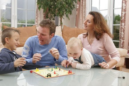 progeny: Young couple with their children playing in the living room