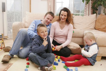 freetime: Young family is playing on the living-room rug