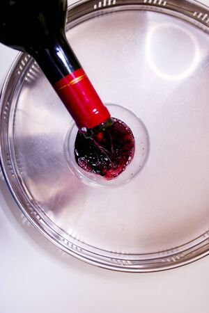 metall and glass: pouring red wine into the glass