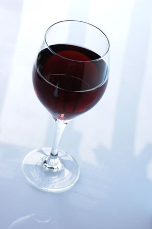 redwine: glass of redwine against lightblue background Stock Photo