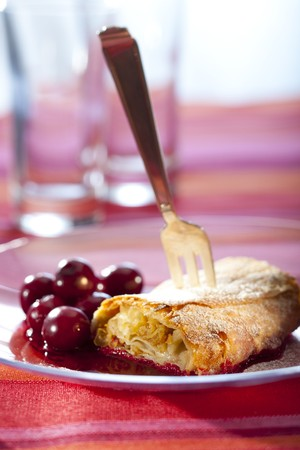 strudel: apple strudel with hot cherries on a plate