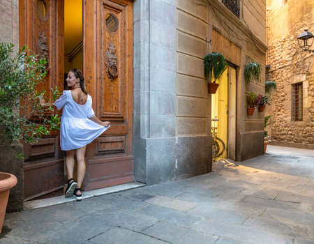 Posing in a white dress in the streets of Barcelona's Gothic Quarter at nightfall