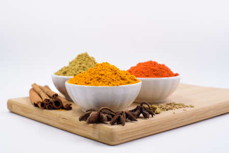 Herbs and spices such as star anise, cinnamon, turmeric, chilli powders and other on a chopping board