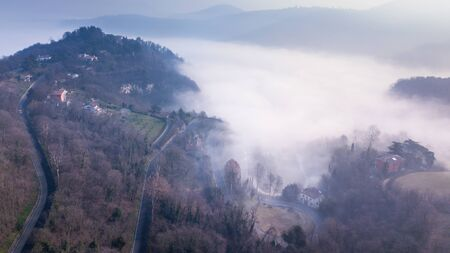 a view of a foggy village from above Фото со стока