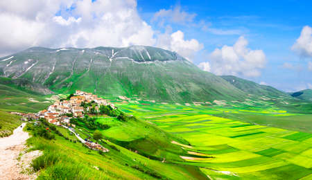 green fields: beautiful landscapes and villlages of Italy - Castelluccio di norcia Stock Photo