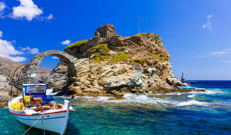 light house: Andros island, old fortress and traditional boat. Greece