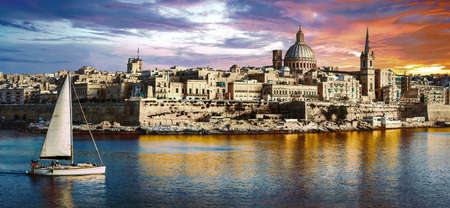 beautiful Valletta town with sail boat over sunset