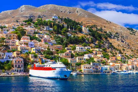 sea of houses: Panoramic view of Symi island, boat, sea and houses, Greece. Stock Photo