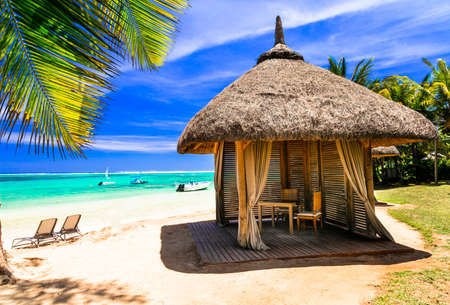 Tropical relaxation in Mauritius Island, view with turquoise sea and bungalow.
