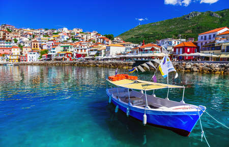 Beautiful Parga village, view with colorful houses and fishing boat, Greece.