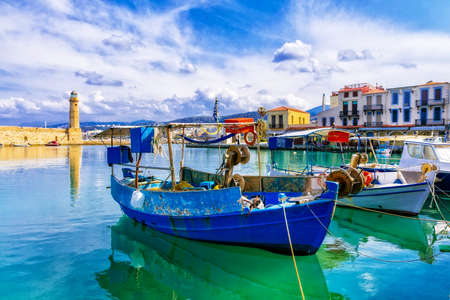 Multicolored Rethymno pier, Greece, view with lighthouses and fishing boats. Imagens