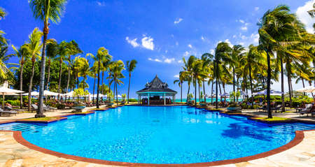 Luxury resort in Mauritius, view with bungalows, palm trees and swimming pool. Stock Photo