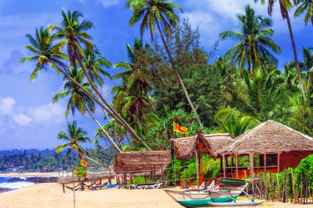 Beautiful Tangalle beach, view with bungalows, palm trees and golden sand, Sri Lanka. Editorial