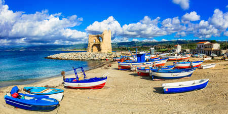 Traditional fishing boats and old tower in Briatico, Calabria, Italy.