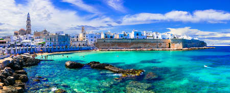 Traditional white houses and tourquise sea in Monopoli town, Puglia, Italy.