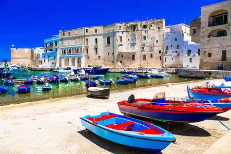 Barche da pesca tradizionali, case e mare nella città di Monopoli, Puglia, Italia.