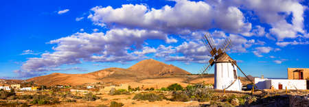 Traditional windmill and mountains on Fuerteventura island, Canary island, Spain Banco de Imagens