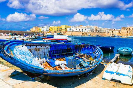 Traditional fishing boats, sea and houses in Gallipoli harbor, Puglia, Italy Banco de Imagens