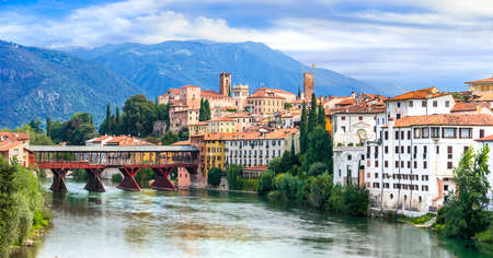 Traditional colorful houses, old bridge and Brenta river, Bassano del Grappa, Veneto region, Italy.