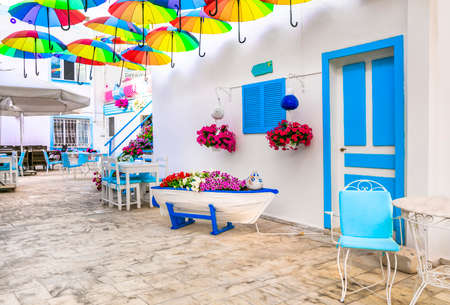Beautiful street bar (restaurant) decoration with colorful umbrellas, old wooden boat and flowers. Bodrum,Turkey Publikacyjne