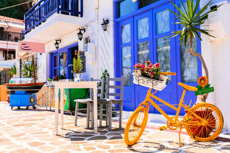 Greece street taverns decorated with flowers and old bicycle.