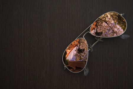 Sunglasses on the wood ,sky and tress is reflected in the glasses Stock Photo