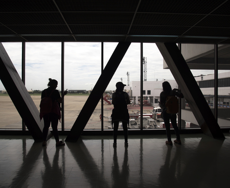 airport window: Silhouette traveler woman at the airport window Stock Photo