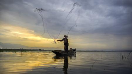 Fisherman of Bangpra Lake in action when fishing in the sunshine morning, Thailand