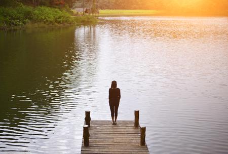 Vrouw voelen zich overweldigend op de brug in het meer, Thailand Stockfoto